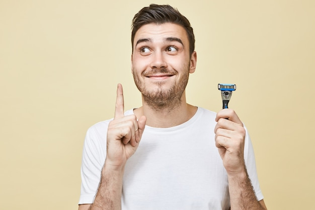 Happy emotioanl young man with beard posing  wearing white t-shirt holding raised finger as if having good idea while shaving face in bathroom, using razor stick, looking up and smiling