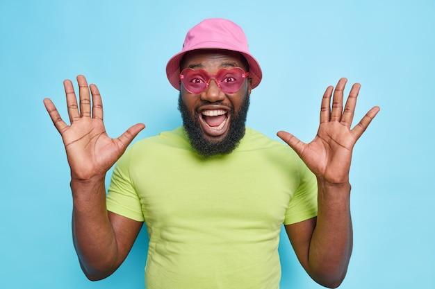 Felice ragazzo barbuto emotivo alza i palmi si sente molto contento esclama reagisce ad alta voce a notizie incredibili indossa eleganti occhiali da sole rosa maglietta casual e panama isolato sul muro blu
