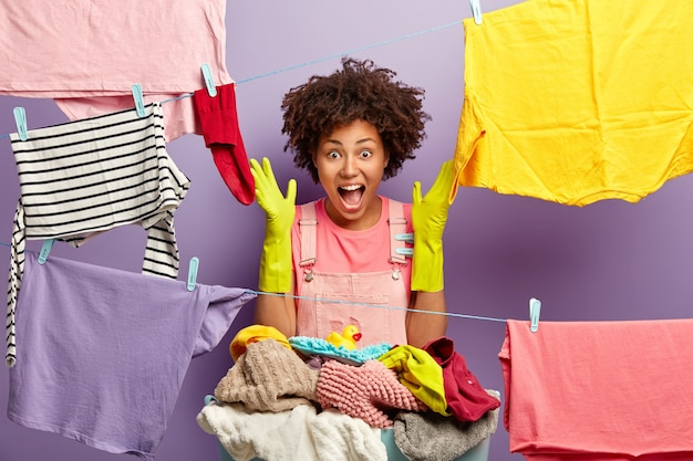 Happy emotional busy young woman exclaims loudly, raises hands in rubber gloves, hangs clean laundry on clothesline with pegs, has busy washing day, isolated on purple wall. housekeeping concept