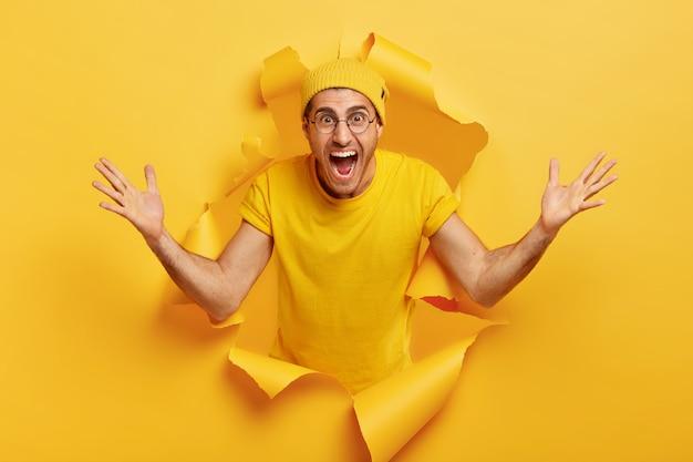 L'uomo caucasico emotivo felice mostra un gesto enorme, misura qualcosa di grande