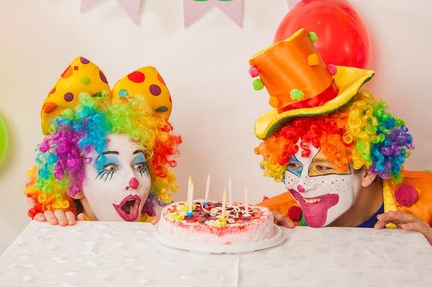 생일 케이크를 먹으려 고하는 휴일에 행복한 감정적 광대