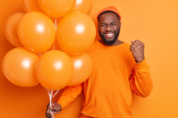 Happy emotional dark skinned bearded guy clenches fist and teeth celebrates getting promotion spends free time at party
