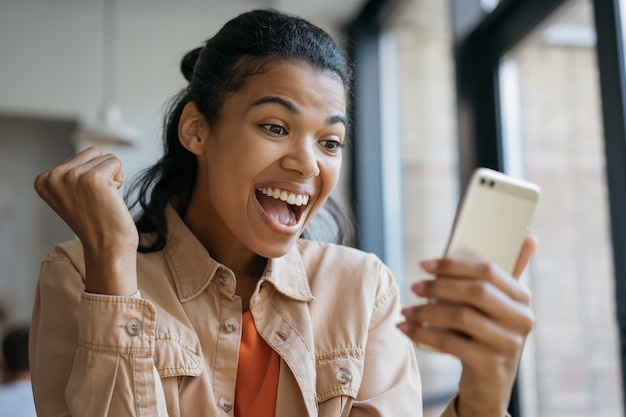 Happy emotional girl celebrates victory, sports betting concept. young excited african american woman shopping online with cash back