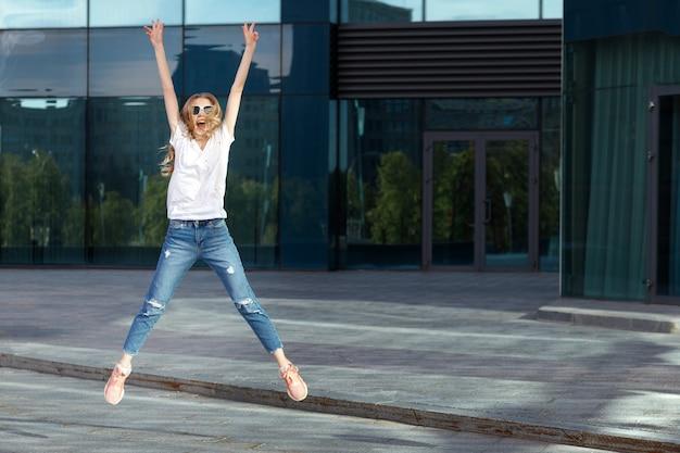 Счастливая эмоциональная девушка в белой футболке прыгает и смеется летом в городе