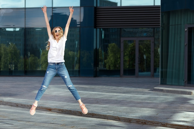 Happy emotional girl in a white tshirt jumps and laughs summer in the city