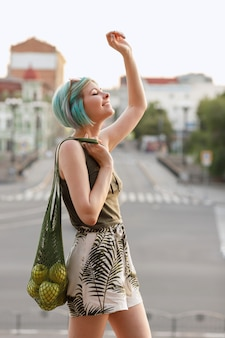 Happy emotional girl with multicolored hair and a shopper with apples in the city in the summer on a walk. gender