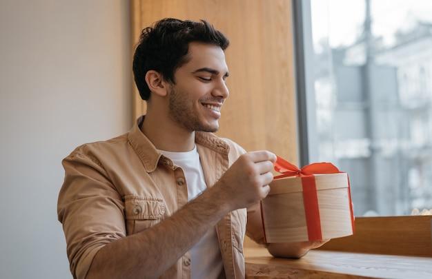 Счастливый эмоциональный индийский мужчина открывает подарочную коробку