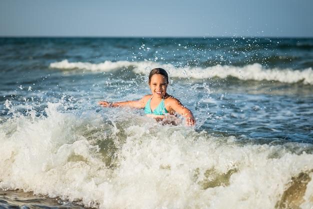幸せな感情的な少女は、晴れた暖かい夏の日に泡立つ嵐の海の波を浴びます。待望の休暇と子供との旅行のコンセプト