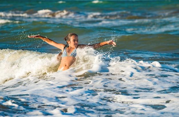 幸せな感情的な少女は、晴れた暖かい夏の日に泡立つ嵐の海の波を浴びます