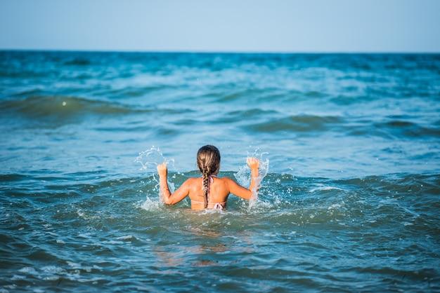 幸せな感情的な少女は、晴れた暖かい夏の日に泡立つ嵐の海の波を浴びます。
