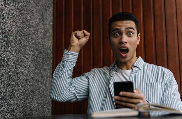 スマートフォンを使用して幸せな感情的な男、オンライン宝くじに勝つ