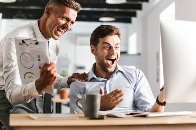 Счастливые эмоциональные коллеги мужчин в офисе, работающем с компьютером.