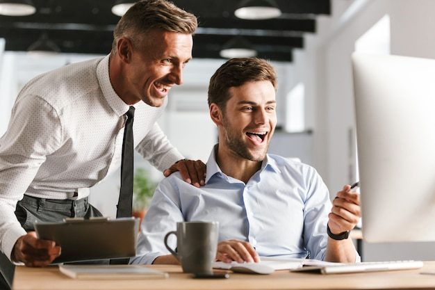 Happy emotional men colleagues in office working with computer.