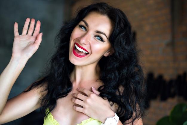 幸せなブルネットの女性の笑顔と笑い、青い目と明るいメイクの幸せな感情的な肖像画。
