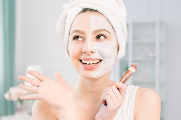 Happy and emotional spa girl applying face mask. aesthetic procedure. the girl applies an anti-aging mask of clay on half of the face with a brush