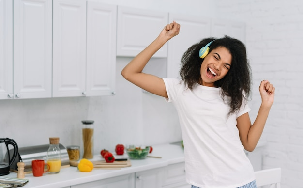Happy emotional woman dancing at home, having fun. portrait of beautiful african american girl listening music using wireless headphones