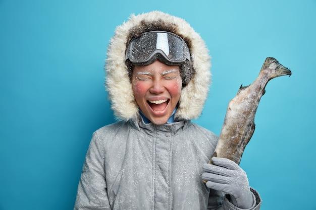 붉은 얼굴을 가진 행복한 감정 여성은 잡힌 물고기가 겨울 휴가를 즐기고 겉옷을 입고 활동적인 휴식을 취하면서 기꺼이 외칩니다.