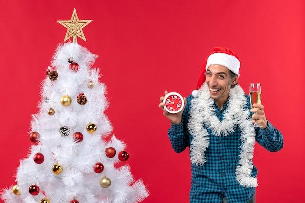 サンタクロースの帽子とワインのグラスを上げて保持している幸せな感情的な若い男