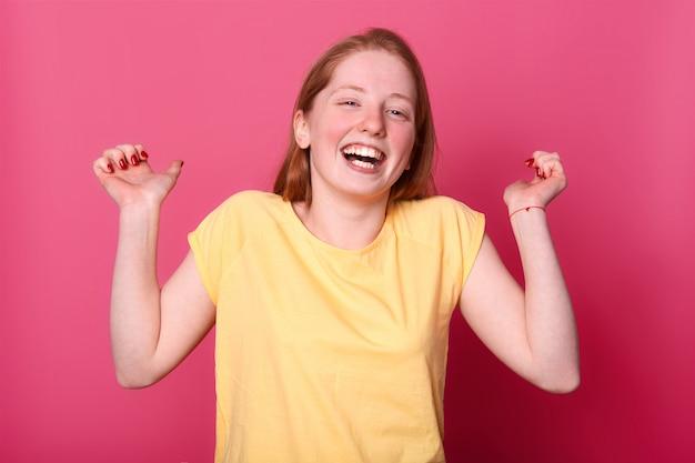 Счастливая эмоциональная молодая женщина в ярко-желтой майке искренне смеется, поднимает руки, слышит забавную шутку, любит проводить время и веселиться со своими друзьями. концепция эмоций людей