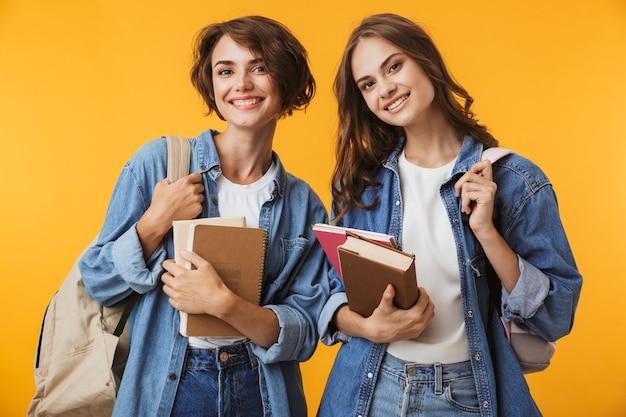 本を保持している黄色の壁の上に孤立してポーズをとって幸せな感情的な若い女性の友人。