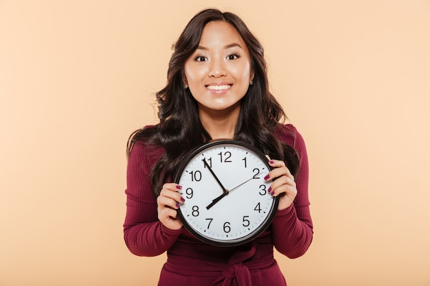 Happy emotions of asian woman with curly long hair holding clock showing nearly 8 waiting for something pleasant over peach background