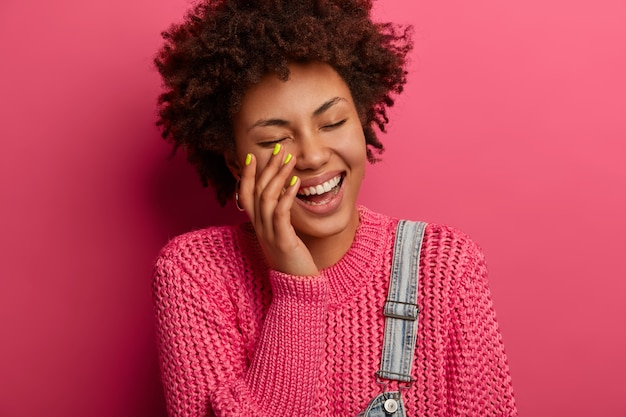 Happy emotions and feelings concept. joyful curly african american woman laughs out from hearing hilarious joke, smiles broadly, being entertained by funny friend, dressed casually, poses indoor