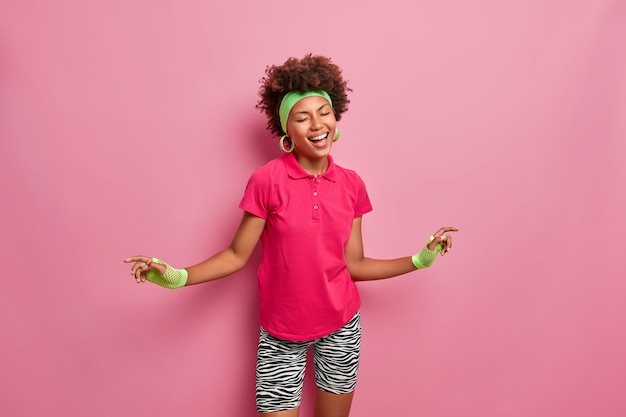 Felici emozioni e concetto di stile di vita. allegra donna sportiva dalla pelle scura balla con gioia, vestita in abbigliamento sportivo, essendo energica