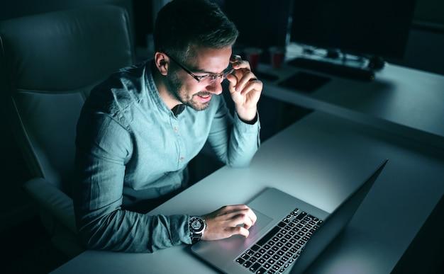Счастливый работник, используя ноутбук для работы над проектом, сидя в офисе поздно ночью.