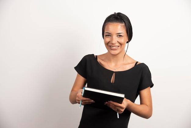 白い壁に笑顔のノートブックと幸せな従業員。