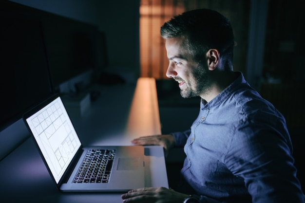 Счастливый сотрудник работает над проектом и сидит в офисе поздно ночью.