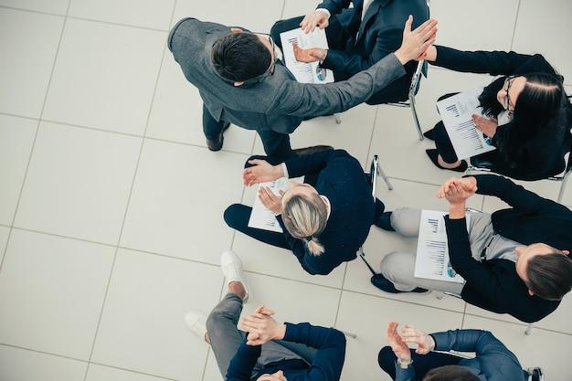 Счастливые сотрудники, давая друг другу пять на рабочем совещании