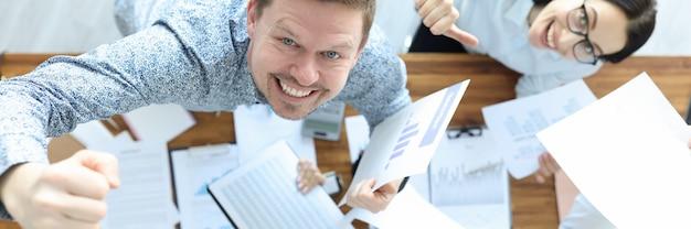 Счастливые сотрудники в офисе держат финансовые документы и позитивный жест делового успеха