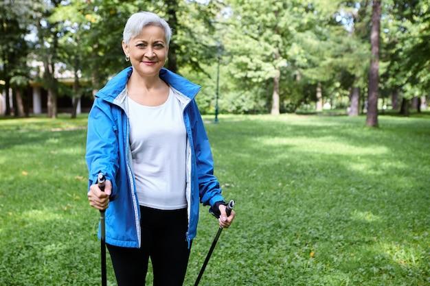Pensionato femminile attivo energico felice in giacca blu che gode del nordic walking utilizzando pali appositamente progettati, respirando aria fresca all'aperto. attività fisica, stile di vita sano, persone e invecchiamento