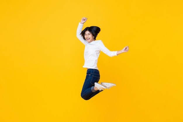 Happy energetic asian woman jumping in mid-air
