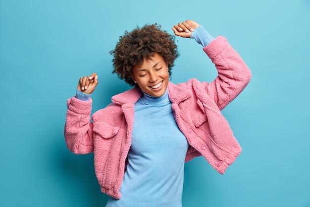 幸せでエネルギッシュな浅黒い肌の女性がリズミカルな音楽に合わせて踊り、腕を上げる