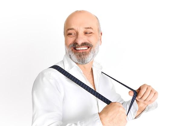 Felice energico pensionato maschio con la barba lunga si prepara per uscire indossando abiti eleganti ed eleganti, ridendo, tirando le cinghie delle parentesi graffe