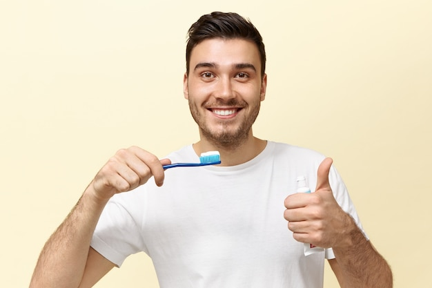 Happy energetic young european guy with stubble holding tooth brush with whitening paste and showing thumbs up gesture being in good mood.
