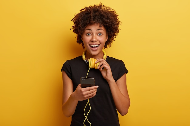 Happy enthusiastic female holds smart phone device connected to stereo headphones, smiles positively