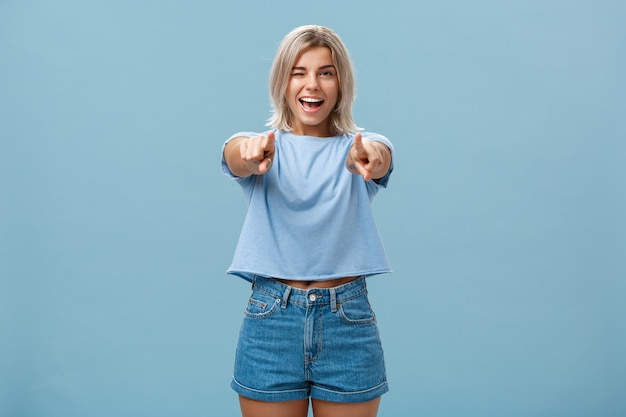 Happy enthusiastic stylish blonde female picking or making hint smiling joyfully and winking from amazement and happiness posing over blue wall