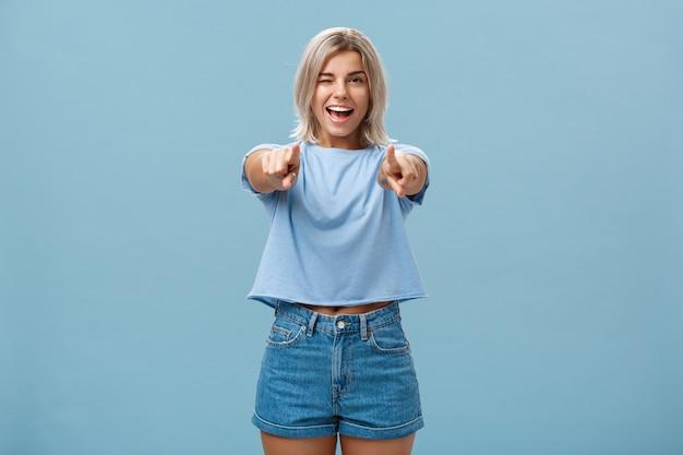 幸せな熱狂的なスタイリッシュな金髪の女性が喜んで笑って、青い壁にポーズをとって驚きと幸せからウィンクするヒントを選んだり、
