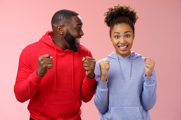 Happy enthusiastic thrilled young african american couple clenching fists joyfully surprised winning awesome honeymoon trip tickets standing pink background triumphing smiling broadly celebrating