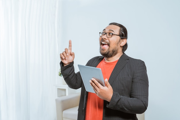 Happy entrepreneur pointing his finger up and hold tablet pc