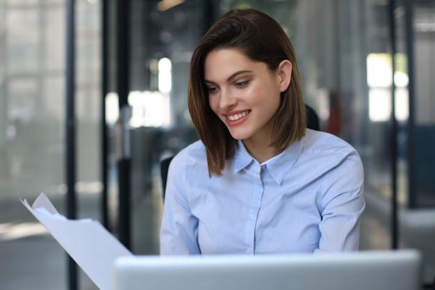 행복한 기업가 여성은 포스트 페이퍼 서신에서 좋은 소식을 읽는 책상에 앉아 있습니다.
