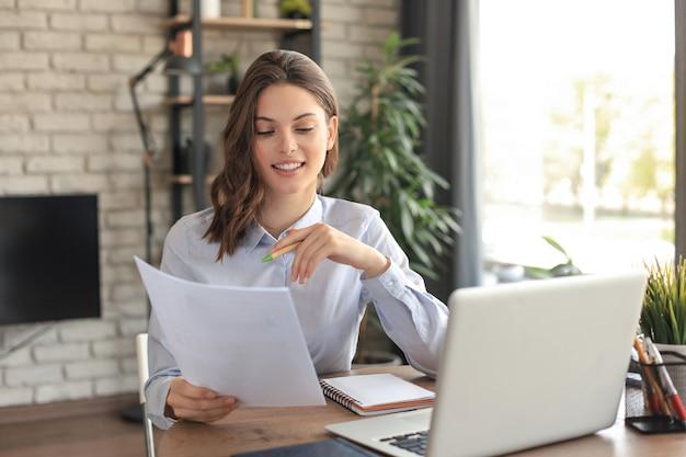 Счастливая женщина-предприниматель сидит за столом, читая хорошие новости в почтовой корреспонденции.