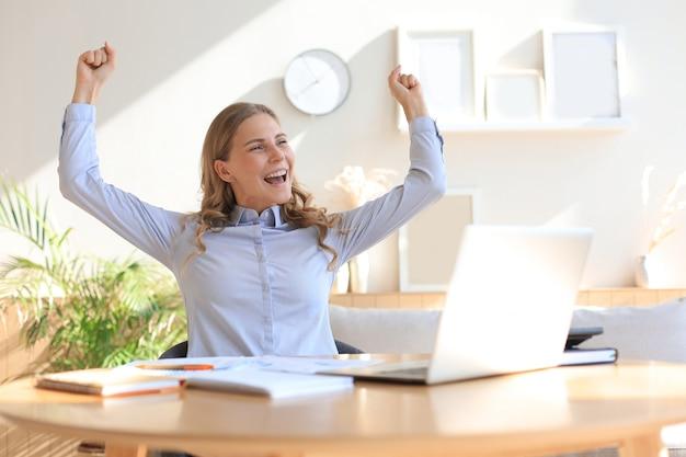 Happy entrepreneur woman sit at desk reading good news and express joy rising hands up.