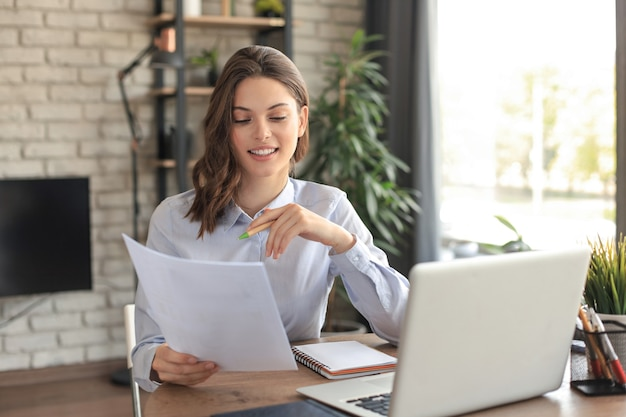 Happy entrepreneur woman sit at desk reading good news in post paper correspondence.
