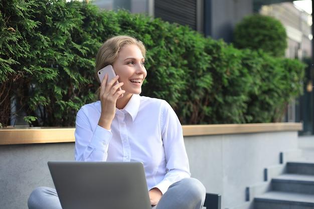 Счастливый предприниматель, работающий с телефоном и ноутбуком возле офиса.