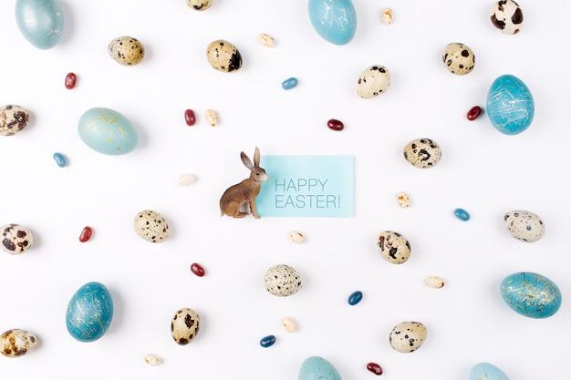 해피 에스테르 카드입니다. 흰색 배경에 부활절 토끼 장식 메추라기, 금색과 파란색 부활절 달걀. 평평한 평지, 평면도. 부활절 개념입니다.