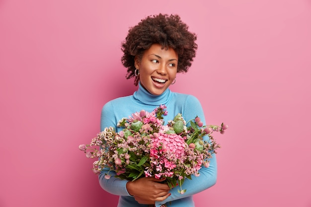 Happy ethnic afro american woman embraces big bouquet of flowers, smiles broadly