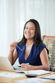 Happy ethnic businesswoman at table in office